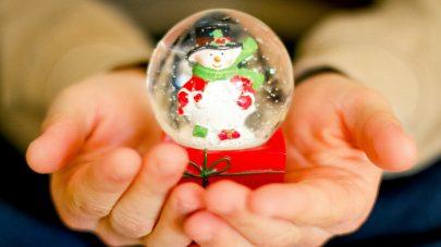 hands holding snowman snow globe